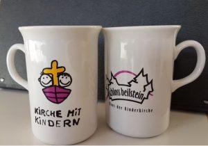 zwei weiße Tassen mit Logo