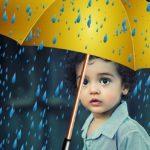 Kind mit gelbem Schirm im Regen